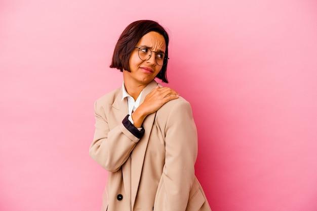 Gemischte rassenfrau des jungen geschäfts lokalisiert auf rosa wand, die einen schulterschmerz hat
