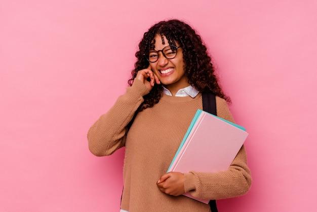 Gemischte rassenfrau des jungen studenten lokalisiert auf rosa hintergrund, der ohren mit händen bedeckt.