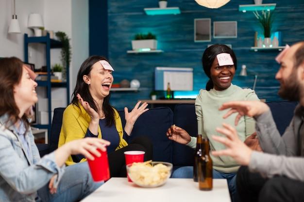 Gemischte rassenfreunde, die brettspiele mit haftnotizen spielen, verbringen spät in der nacht zeit miteinander und entspannen sich auf der couch im wohnzimmer. gruppe multiethnischer menschen, die bier trinken, pommes essen und zu hause p genießen