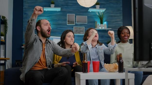 Gemischte rassenfreunde, die sich auf der couch entspannen und fußballspiele während des sportwettbewerbs ansehen. fröhliche gruppe von gemischtrassigen menschen, die die gemeinsame zeit genießen, spät in der nacht im wohnzimmer fußballtor zu feiern