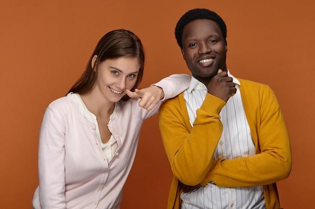 Gemischte rassenkulturen, interraciale liebe, beziehungen und kooperationskonzept. bild der glücklichen aufgeregten jungen europäischen frau mit losem haar und afrikanischem mann mit den perfekten zähnen lächelnd, überglücklich