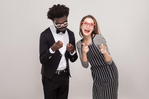 Gemischte rassenpaare, die mit den fingern auf die kamera zeigen und lächeln. studioaufnahme, grauer hintergrund
