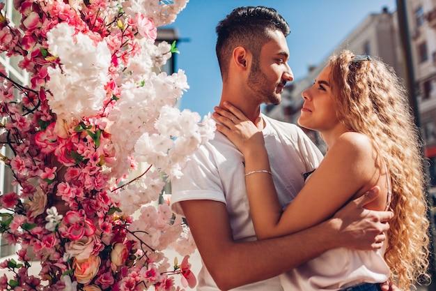 Gemischte rassenpaare, die sich im freien umarmen. arabischer mann und weiße frau, die in die stadt gehen. romantische beziehungen