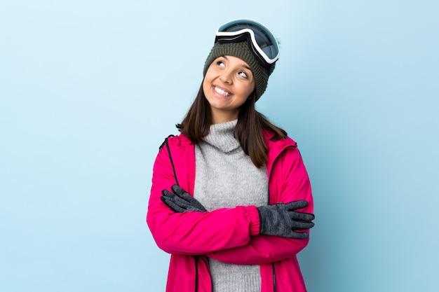 Gemischte renn-skifahrerin mit snowboardbrille über isolierter blauer wand, die beim lächeln nach oben schaut