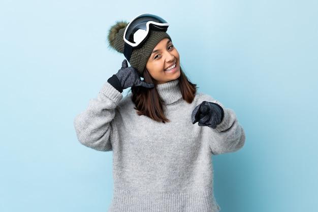 Gemischte rennskifahrerin mit snowboardbrille über blauer wand, die telefongeste macht und nach vorne zeigt.