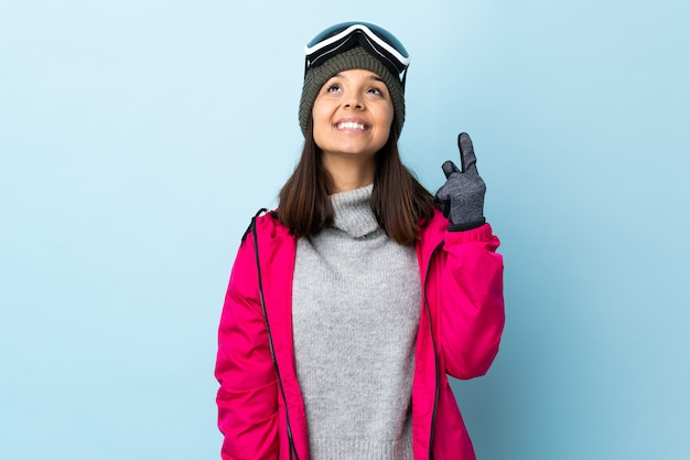 Gemischte rennskifahrerin mit snowboardbrille über der blauen wand, die nach oben zeigt und überrascht.