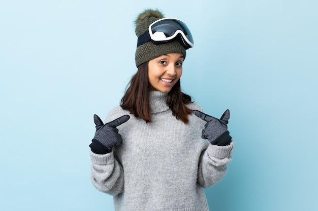 Gemischte rennskifahrerin mit snowboardbrille über isolierter blauer wand, die eine daumen hoch geste gibt