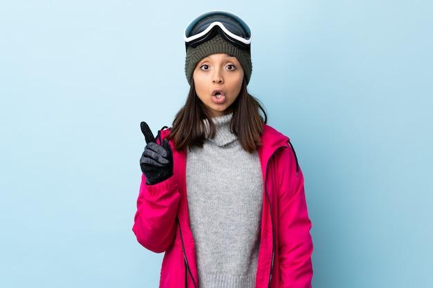 Gemischte rennskifahrerin mit snowboardbrille über isolierter blauer wand, die eine idee denkt, die den finger nach oben zeigt