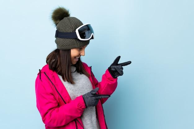 Gemischte rennskifahrerin mit snowboardbrille über isolierter blauer wand, die finger zur seite zeigt und ein produkt präsentiert