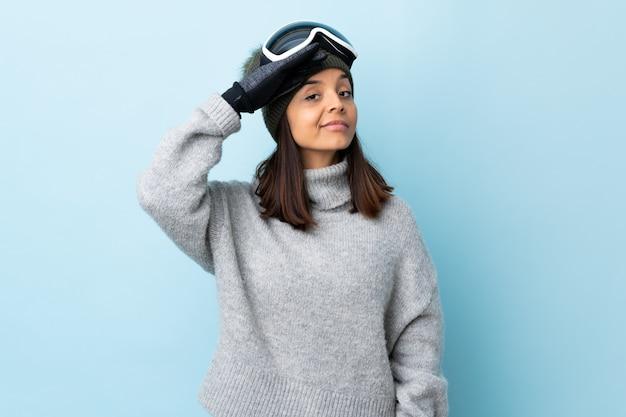 Gemischte rennskifahrerin mit snowboardbrille über isolierter blauer wand, die mit hand mit glücklichem ausdruck salutiert