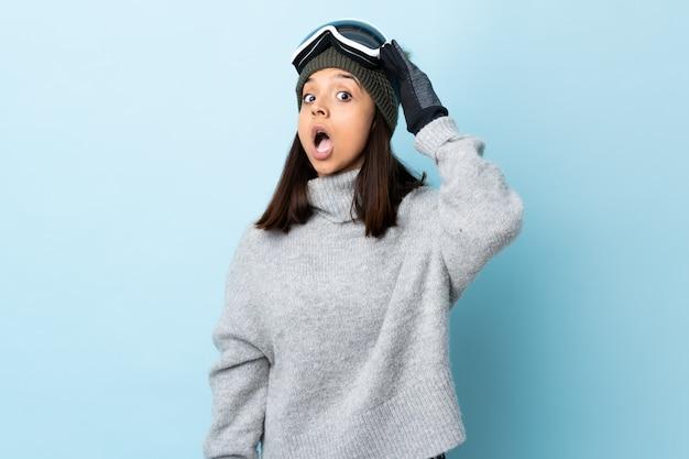 Gemischte rennskifahrerin mit snowboardbrille über isolierter blauer wand, die überraschungsgeste tut, während sie zur seite schaut