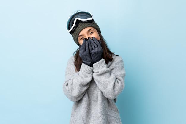 Gemischte rennskifahrerin mit snowboardbrille über isolierter blauer wand glücklich und lächelnd, mund mit händen bedeckend