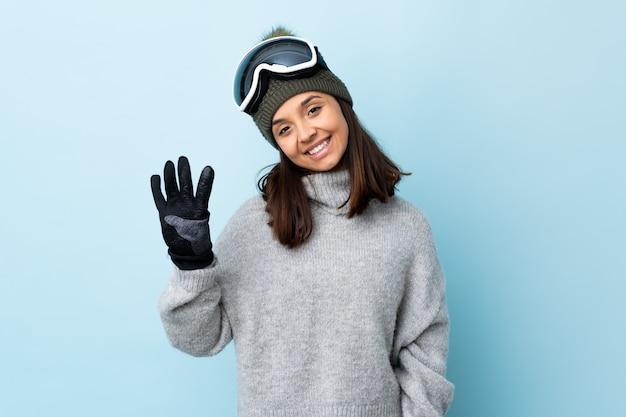 Gemischte rennskifahrerin mit snowboardbrille über isolierter blauer wand glücklich und zählt vier mit den fingern