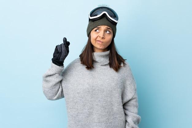Gemischte rennskifahrerin mit snowboardbrille über isolierter blauer wand mit den fingern, die kreuzen und das beste wünschen