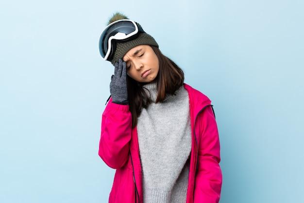Gemischte rennskifahrerin mit snowboardbrille über isolierter blauer wand mit kopfschmerzen