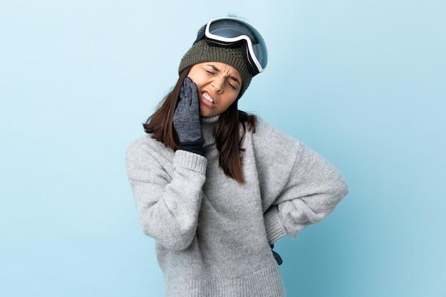 Gemischte rennskifahrerin mit snowboardbrille über isolierter blauer wand mit zahnschmerzen