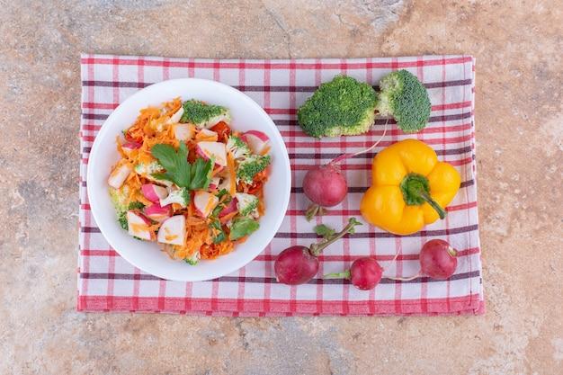 Gemischte salatteller neben verschiedenen gemüsesorten auf einem handtuch auf marmoroberfläche