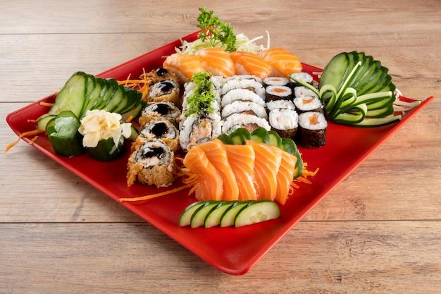 Gemischte sushirolle und lachssashimi auf rotem teller