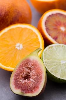 Gemischte zitrusfruchtorange, feigen, limetten auf einem grau