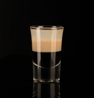 Gemischter alkoholischer schnaps in einem schnapsglas auf schwarzem hintergrund isoliert