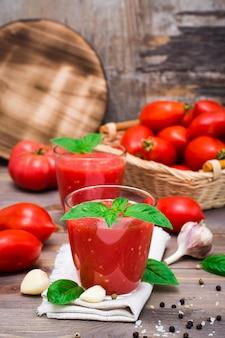 Gemischter frischer tomatensaft mit basilikum verlässt in den gläsern auf einer serviette auf einem holztisch