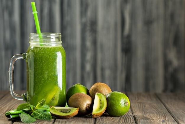 Gemischter grüner smoothie mit bestandteilen auf holztisch