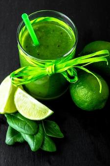Gemischter grüner smoothie mit bestandteilen auf schwarzer tabelle.