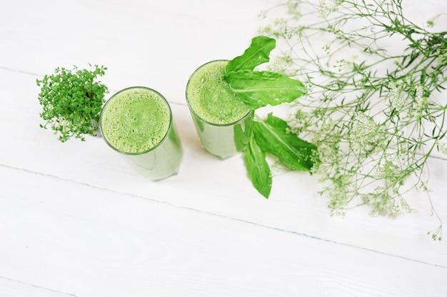 Gemischter grüner smoothie mit bestandteilen oder cocktail auf weißem hintergrund, frühstücksstrenger vegetarier mit einem platz für ihren text, konzept des rohen lebensmittels, detox
