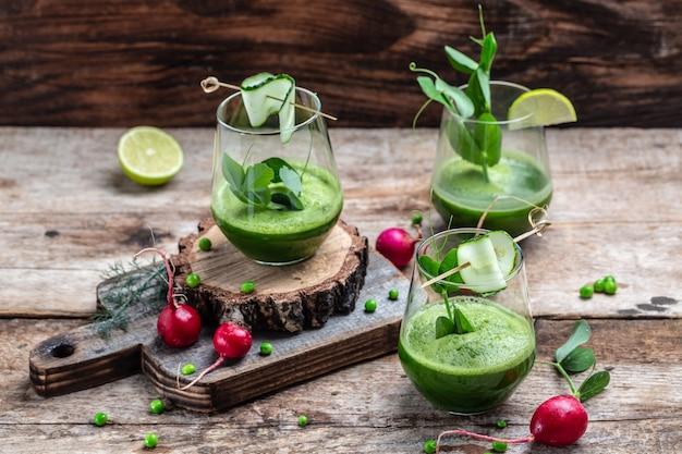 Gemischter grüner smoothie mit zutaten auf holztisch. detox smoothie, grüne frische erbsen, gurke, rettich, spinat und limette. banner, menürezeptplatz für text, draufsicht.