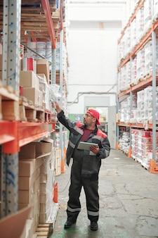 Gemischter lagerarbeiter in uniform scannt qr-codes auf großen kisten, während er im gang neben einem riesigen regal mit verpackter ware steht