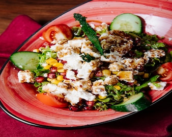 Gemischter lebensmittelsalat mit viel grün, gemüse und weißkäse.