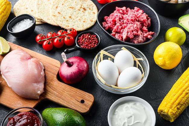 Gemischter mexikanischer lebensmittelhintergrund, rohe organische bestandteile für tacos mit hühner- und rindfleisch, maistortilla, salsa, chili über schwarzem hintergrund, seitenansicht.
