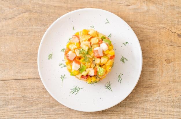 Gemischter obstsalat mit krabbenstäbchen (apfel, mais, papaya, ananas)