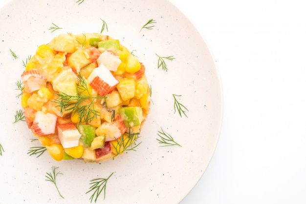 Gemischter obstsalat mit krabbenstange (apfel, mais, papaya, ananas) isoliert auf weiß
