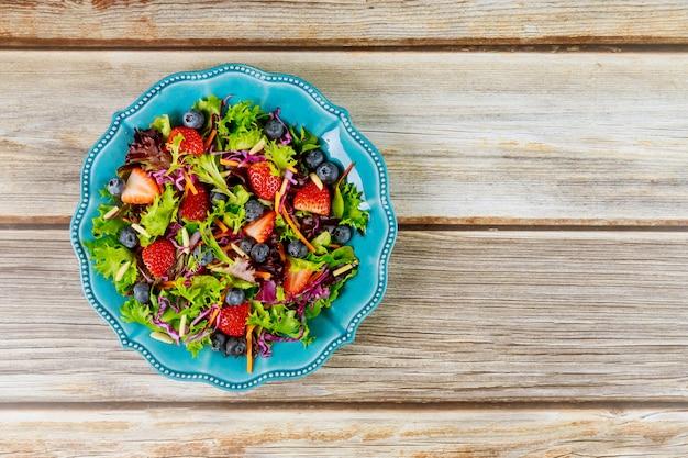 Gemischter salat mit beeren, grünen blättern, karotten, blaubeeren und mandeln
