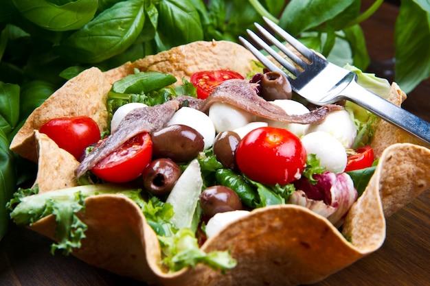 Gemischter salat mit mozzarella und sardellen in einem brotkorb