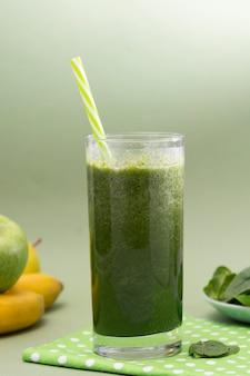 Gemischter selektiver glasfokus des grünen smoothie, grüner hintergrund. gesundes essen.