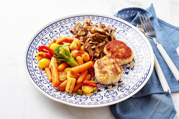 Gemischtes gemüse aus karotten, brokkoli, babymais, paprika, gerösteten champignons und zwei hühnchenpastetchen in semmelbröseln