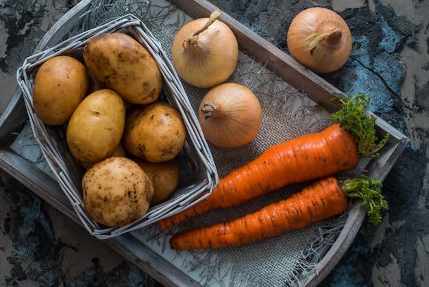 Gemischtes gemüse. kartoffeln, karotten und zwiebeln in einem korb. vegetarisches essen kochen