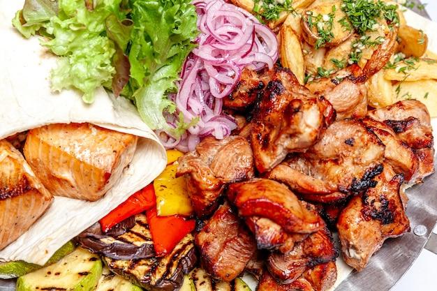 Gemischtes grillfleisch gebratenes gemüse und gegrillte lachsfischfilets dekoration in warmem gericht