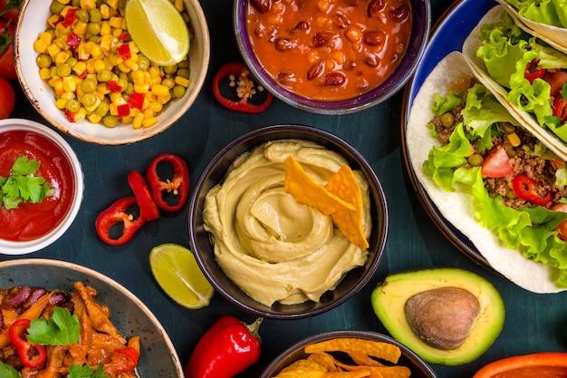 Gemischtes mexikanisches essen. partyessen. guacamole, nachos, fajita, fleisch-tacos, salsa, paprika, tomaten auf einem holztisch. draufsicht.