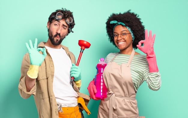 Gemischtes paar, das sich glücklich, entspannt und zufrieden fühlt, zustimmung mit einer guten geste zeigt und lächelt. housekeeping-konzept .. home reparaturen konzept
