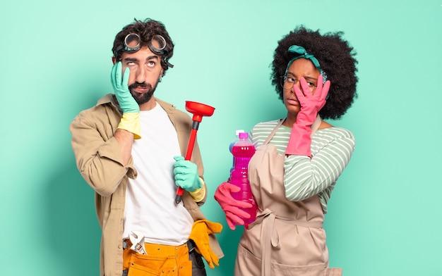 Gemischtes paar, das sich nach einer mühsamen, langweiligen und mühsamen aufgabe gelangweilt, frustriert und schläfrig fühlt und das gesicht mit der hand hält. housekeeping-konzept .. home reparaturen konzept