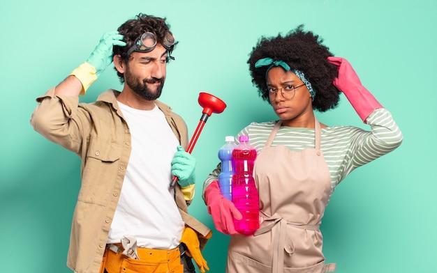 Gemischtes paar, das sich verwirrt und verwirrt fühlt, sich am kopf kratzt und zur seite schaut. housekeeping-konzept .. home reparaturen konzept