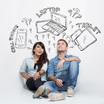 Gemischtes paar, das über elektronik zwischen handy, laptop und tablet nachdenkt
