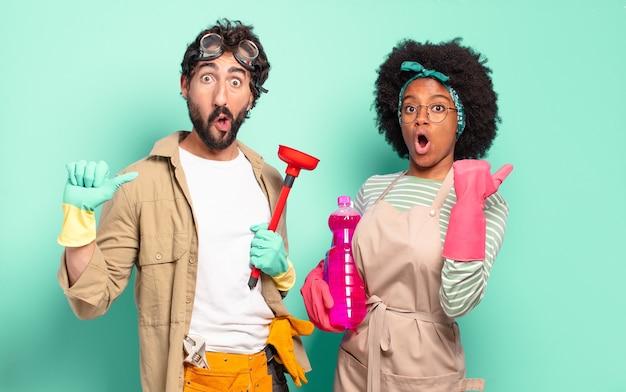 Gemischtes paar, das ungläubig erstaunt aussieht, auf ein objekt auf der seite zeigt und wow sagt, unglaublich. housekeeping-konzept .. home reparaturen konzept