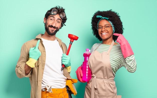Gemischtes paar, das zuversichtlich lächelt und auf ein breites lächeln zeigt, positive, entspannte, zufriedene haltung. housekeeping-konzept .. home reparaturen konzept
