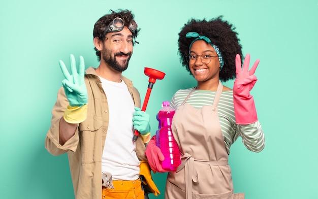 Gemischtes paar lächelt und sieht freundlich aus, zeigt nummer drei oder drei mit der hand nach vorne und zählt herunter. housekeeping-konzept .. home reparaturen konzept