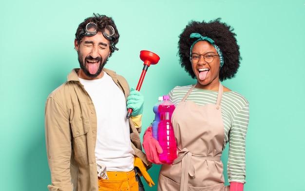 Gemischtes paar mit fröhlicher, sorgloser, rebellischer haltung, scherzend und mit ausgestreckter zunge, spaß haben. housekeeping-konzept .. home reparaturen konzept
