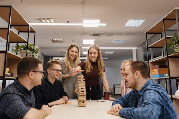 Gemischtes team, das blockholzspiel im büro spielt